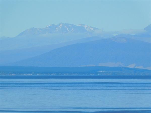만년설이 뒤덮인 높은 산맥을 배경으로 끝이 보이지 않는 타우포 호수(Lake Taupo)