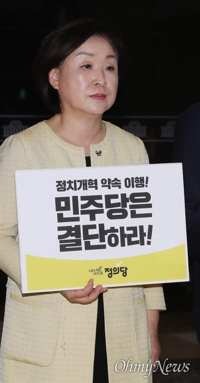 정의당 심상정 대표가 22일 국회 로텐더홀 농성장에서 열린 상무위원회에서 정치개혁 사법개혁 약속이행을 촉구하는 피켓을 들고 있다.