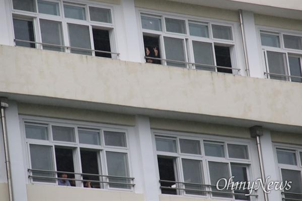 영남공고 정상화를 위한 시민단체공대위가 22일 기자회견을 열고 학교 정상화를 촉구하자 일부 학생들이 창문을 통해 내다보고 있다.