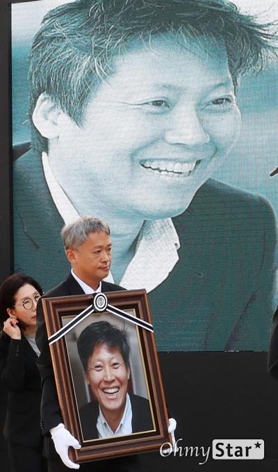 고 이용마 기자, 참언론인의 미소 23일 오전 서울 상암동 MBC 앞 광장에서 열린 <참 언론인 고 이용마 기자 시민사회장>에서 김민식 PD가 고 이용마 기자의 영정사진을 들고 입장하고 있다.