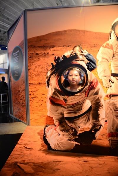 우주인 손녀가 조형물 뒤에서 얼굴을 내민다. 우주인처럼 보인다.