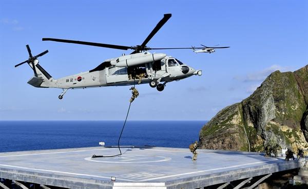 독도서 수호훈련 펼치는 해군 특전요원 25일 독도를 비롯한 인근 해역에서 열린 동해 영토수호훈련에서 해군 특전요원들이 해상기동헬기(UH-60)를 통해 독도에 내리고 있다. [해군 제공]