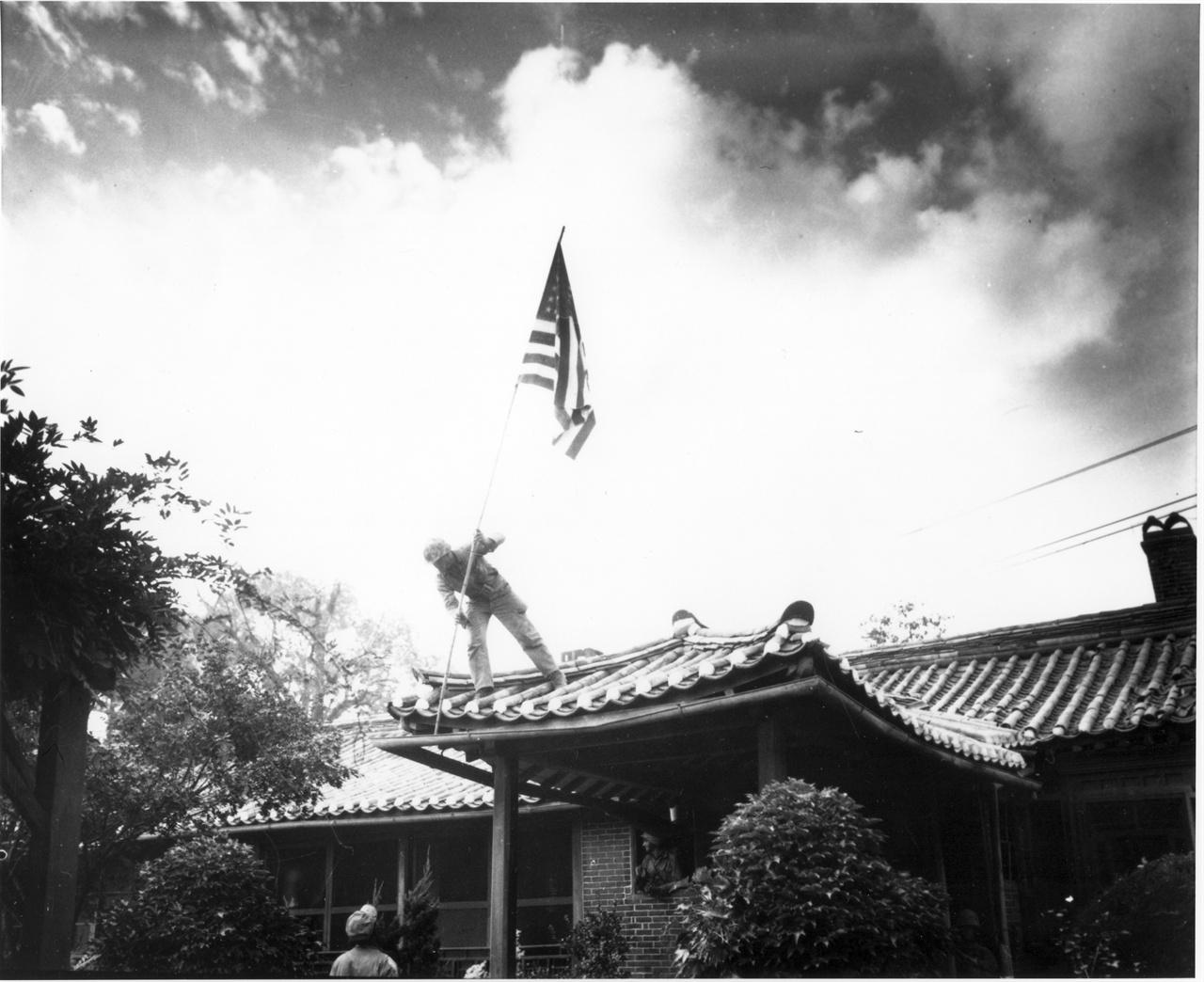 서울, 임시로 마련한 미 대사관 지붕에 성조기를 세우고 있다(1950. 9. 27.).