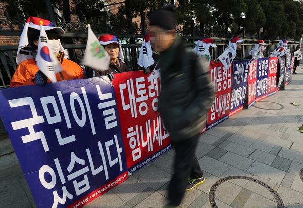 2016년 12월 13일 월드피스자유연합, 4대개혁추진운동본부 관계자들이 서울 종로구 안국역 인근에서 '대통령님 힘내세요' 라고 적힌 피켓을 들고 있다.