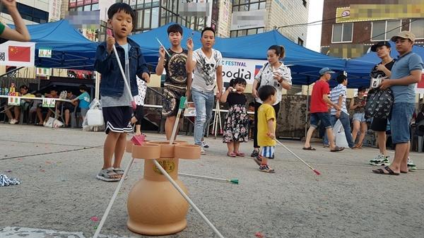 이주노동자들이 행사장에 마련된 전통놀이장에서 투호놀이를 하고 있다.