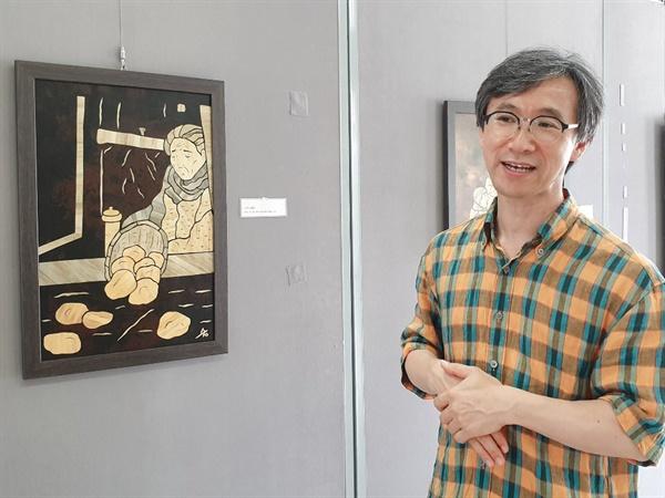 박진우 (재)노무현재단 제주위원회 상임대표가 전시에 대해 설명해주고 있다.왼쪽 작품은 보리아트 이수진 작가의 '소까이'.