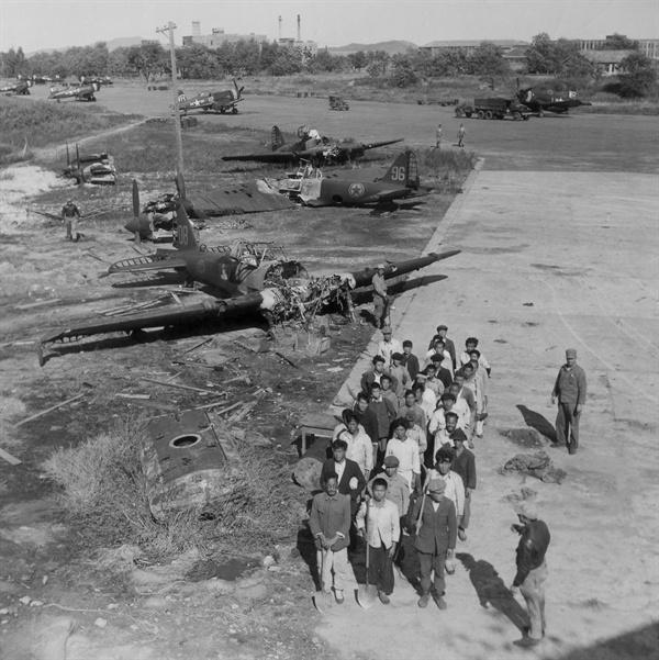 부서진 전투기가 널브러진 비행장으로 노무자들이 일감을 얻고자 몰려들고 있다(1950. 10, 24.).