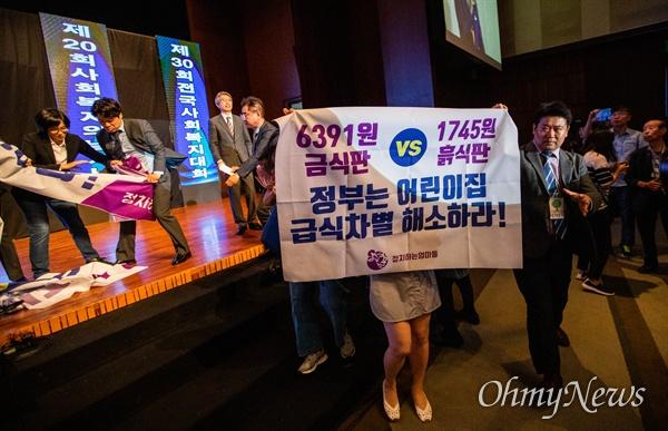정치하는엄마들 회원들이 6일 오전 서울 서의도 63빌딩 컨벤션센터에서 열린 사회복지의날 기념식에서 기습시위를 펼치며 박능후 보건복지부장관을 향해 어린이집 급,간식비 인상을 요구하고 있다.