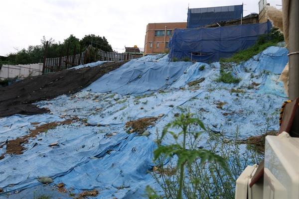 """상도유치원 붕괴 사고 원인으로 지목됐던 인근 다세대주택 공사장 모습. 2018년 12월 진상조사위는 보고서를 통해 사고의 직접적인 원인에 대해 """"상도유치원 건축물은 구조적으로 문제가 없었으나, 건설 현장의 흙막이 붕괴로 건축물의 지반이 훼손되면 붕괴된 것으로 판단된다""""고 밝혔다. 사고 당시 주저앉은 지반 토사 위로 파란색 방수포가 덮여 있다."""