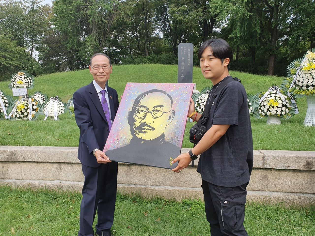 차리석 선생 묘역 앞에서 열린 '차리석 그라피티 작품 헌정식'에서 차영조 회장과 레오다브 최성욱 작가가 함께 작품을 들고 있다.