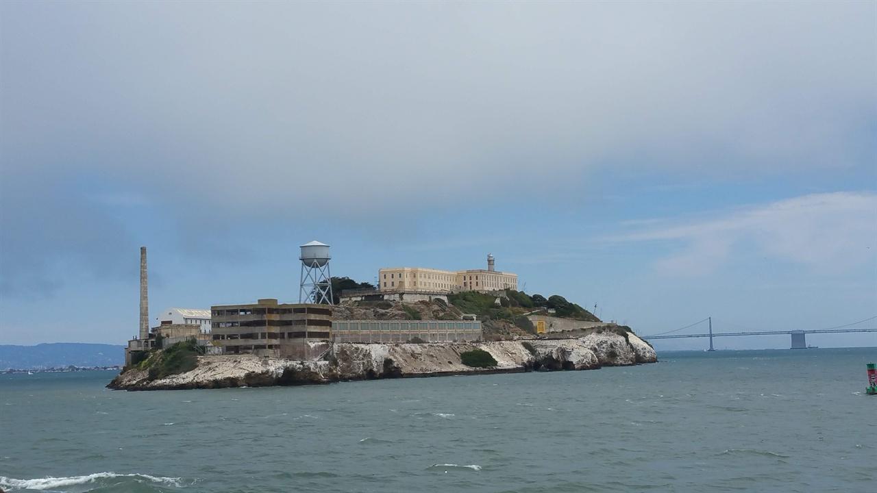 배에서 본 알카트래즈섬 섬 위부분의 큰 건물이 연방 교도소이고 그 위로 보이는 탑이 등대이다. 섬 좌측에는 섬에 전기를 공급하는 발전소와 물을 저장하는 물탱크가 있다.