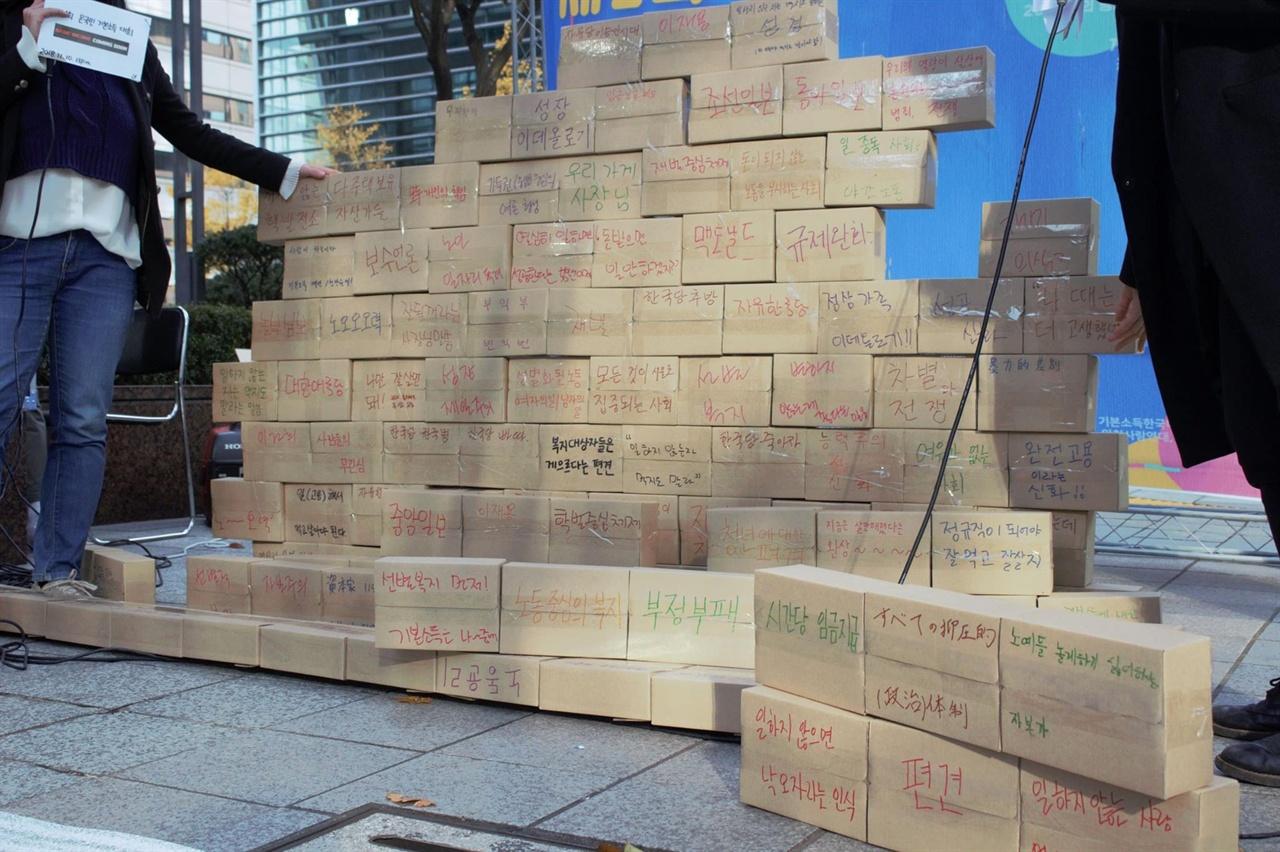 """2018년 11월 10일 진행된 기본소득정치연대 외 단체들이 주최한 <온국민기본소득대회>. 각자가 생각하는 """"기본소득 실현을 가로막는 이유""""를 상자에 쓴 후, 벽을 만들어 사회자가 무너뜨리고 있다."""