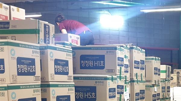 한 대형마트 창고에서 노동자가 명절 선물세트 상품 상자 위에 올라가서 물건을 내리고 있다.