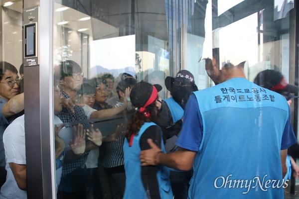 한국도로공사 본사 1층에서 수납원 노동자들이 출입문을 밀고 들어오려고 하자 본사 직원들이 문을 막아 대치하고 있다.