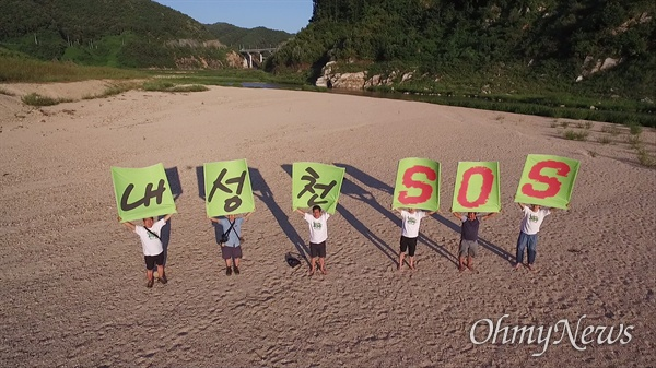 4대강 사업 관련 낙동강 현장조사팀이 지난 8월 30일 경북 영주댐 상류 내성천 모래톱에서 '내성천 SOS' 현수막을 들고 있다.