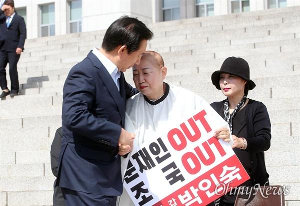 박인숙 자유한국당 의원이 11일 오전 서울 여의도 국회 본관 앞에서 조국 법무부 장관 임명에 항의하며 삭발하자, 김성태 의원이 격려 방문해 박 의원을 위로하고 있다.