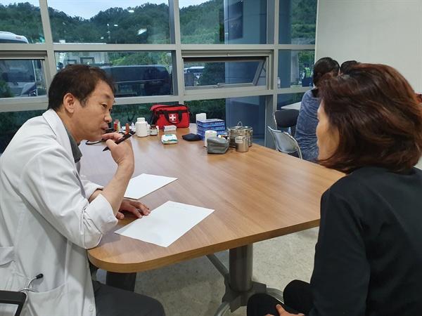 11일 인도주의실천의사협의회 노태맹 성주효병원 원장이 농성 과정에서 부상을 입은 수납원 노동자를 진료하고 있다.