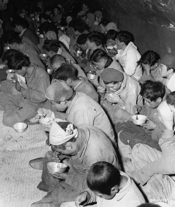 경기도 구리, 인민군 포로와 인민군 부역 혐의로 체포된 이들이 임시수용소에서 식사를 하고 있다(1951. 1. 12.).