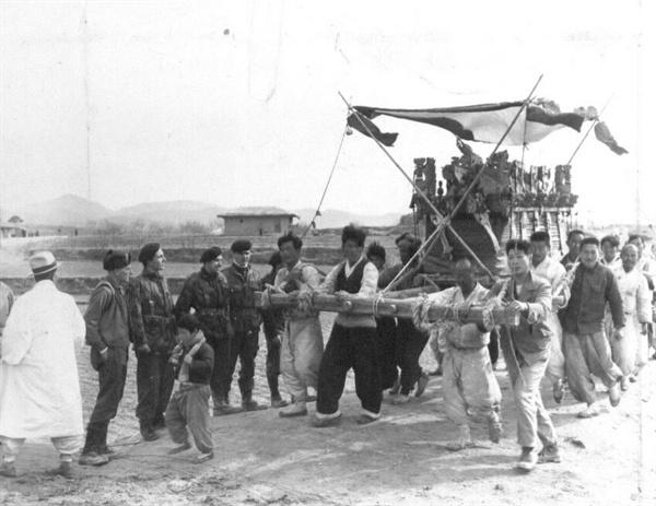 유엔군들이 상여가 나가는 것을 신기하게 바라보고 있다(1951. 1. 23.).