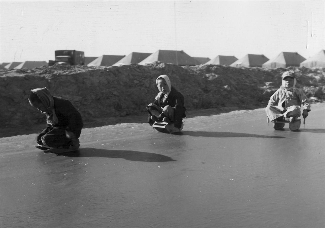 미 해병대부대 옆 빙판에서 한국어린이들이 신나게 썰매를 타고 있다(1951. 1. 28.).