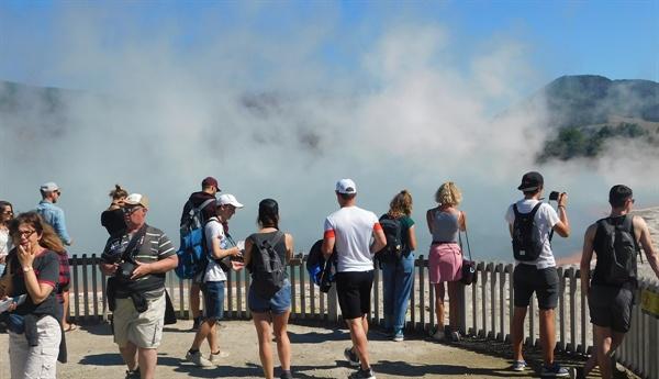 유황냄새가 요동치는 간헐천을 돌아보는 관광객