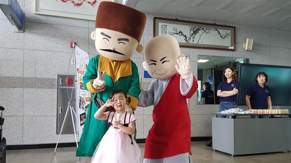 고향을 찾은 귀성객들에게 오는 27일부터 3일간 열리는 '홍성역사인물축제'를 적극적으로 홍보하는 가운데, 한 어린이가 백야 김좌진 장군과 만해 한용운 선사와 함께 사진을 찍고 있다.
