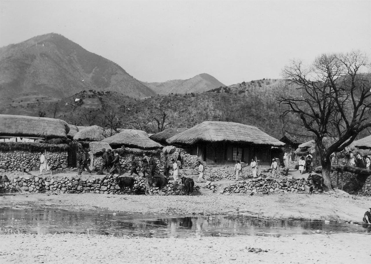 노무자들이 유엔군 군수물자를 지고 마을을 지나고 있다(1951. 2. 4.).