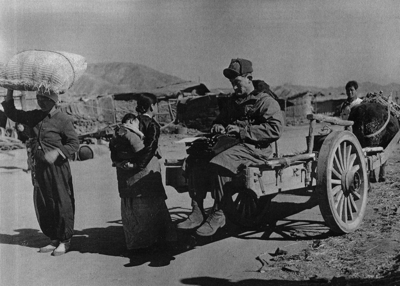 한 유엔군 측 종군기자가 소달구지 위에서 피란민 여인과 면담하면서 기사를 타이핑하고 있다(1951. 2. 6.).