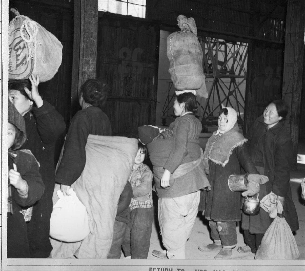 남해안 섬으로 가는 배를 기다리는 피란민들(1951. 2. 8.).