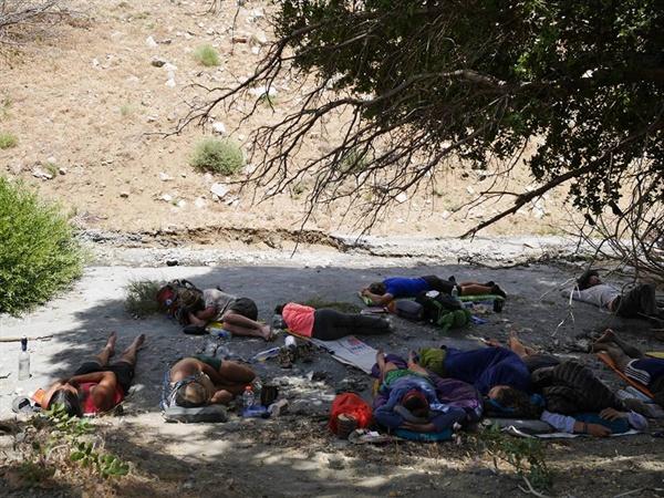 휴식 사막의 뜨거운 태양을 피해 나무그늘 아래 휴식을 취하는 하이커들