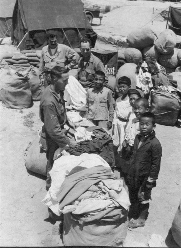 미군들이 한국인에게 구제품을 나눠주고 있다(1951. 7. 3.).