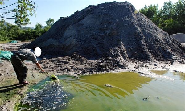 일본에서 수입한 석탄재가 공장 뒷산에 가득 쌓여 있고 비까지 맞아 침출수가 발생한 모습이다.