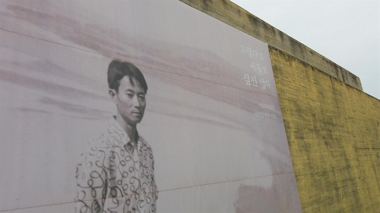 """문학관 외벽에 걸린 시인 사진 1962년 낙화암에서 찍은 사진이다. 사진 오른쪽 윗부분에 """"그렇다고 서둘고 싶진 않다""""라는 문구가 쓰여 있다."""