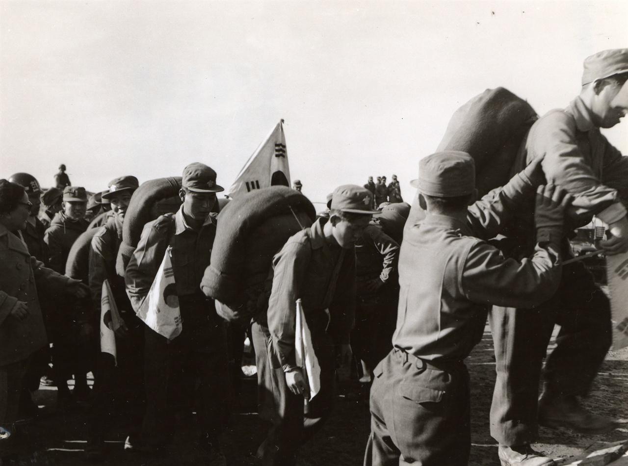 본국 송환을 거부하고 제3국 행을 희망한 포로들이 인천항으로 가고자 화물차에 오르고 있다(1954. 1. 20.).