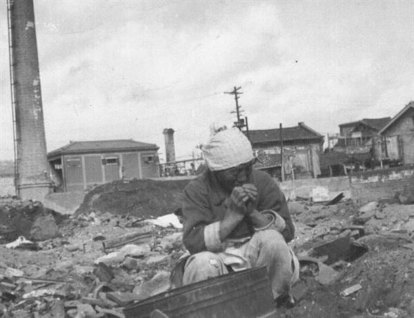 서울, 한 할머니가 폐허의 더미에서 쓸 만한 물건을 찾고 있다(1950. 11. 1.).
