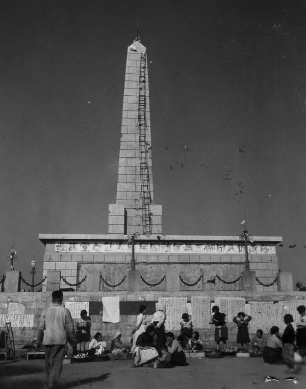 원산, 공산주의 선전탑 언저리에 과일을 파는 장사꾼들. 벽에는 각종 포고문들이 너절하게 붙어 있다(1950. 11. 1.).