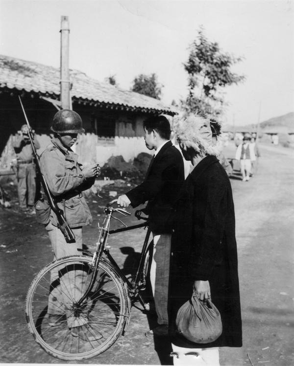원산, 국군이 지나가는 민간인들을 검문하고 있다(1950. 11. 2.).