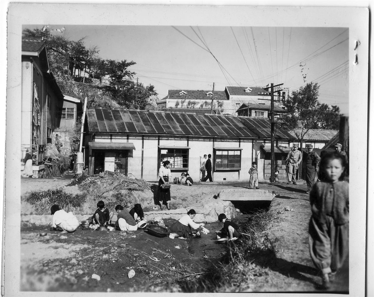 원산, 부녀자들이 동네 냇가에서 빨래를 하고 있다(1950. 11. 1.).