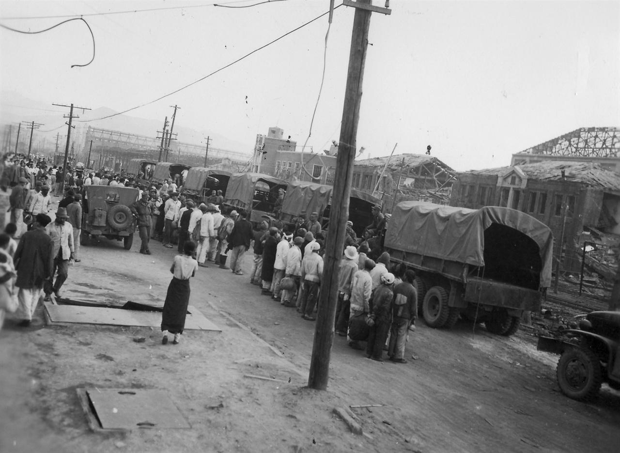 흥남, 미군부대에서 일할 노무자들을 트럭에 실어가고 있다(1950. 11. 8.).
