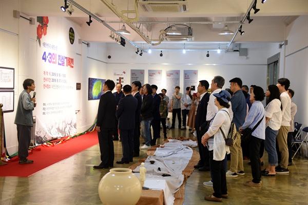 박진우 (재)노무현재단제주위원회 상임대표가 개막행사에 참석한 이들에게 전시에 대해 설명하고 있다.