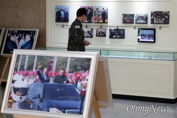 비무장지대(DMZ) 내 유해 발굴 작전에 참여한 군인이 19일 오전 서울 종로구 남북회담본부에서 열린 '9.19 평양공동선언 1주년 기념행사'에 참석해 문재인 대통령과 김정은 위원장의 사진을 관람하고 있다.