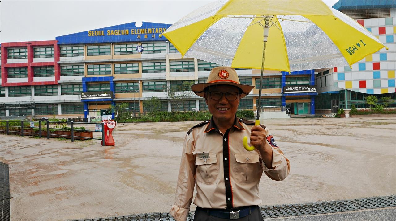 오형완 사근초 학교보안관. 학교 아이들 이름을 모두 기억하고 있다.  경비실(보안관실)에선 비오는 날 우산을 아이들에게 빌려준다. 운동장에선 아이들은 수업전, 그리고 오전 두 시간 수업후에도 놀 수 있다.