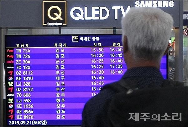 제17호 태풍 타파가 북상중인 21일 오후 한 승객이 제주공항 3층 대합실에서 항공기 운항 안내 화면을 주시하고 있다.