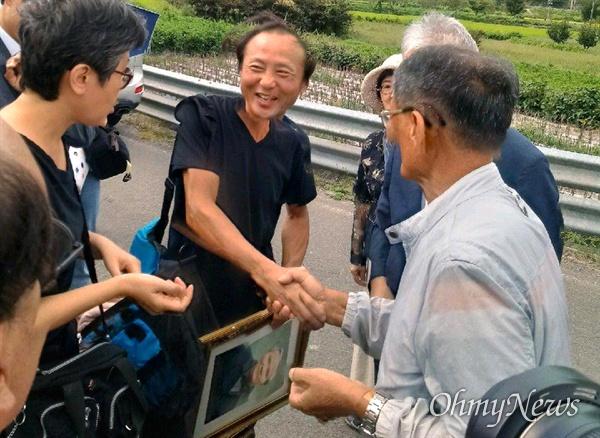한일시민교류단 회원들이 의령 출신인 고 서정우 선생의 친족묘지를 찾아 참배했다. 사진은 서정우 선생의 아들이 아버지의 사진을 들고 친척들을 만나 인사하는 모습.