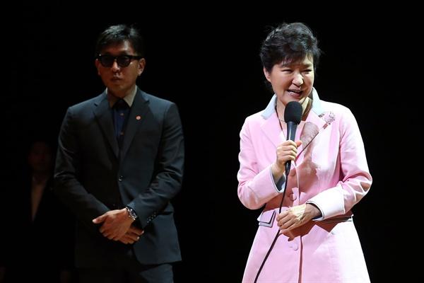 2014년 8월 27일 당시 박근혜 대통령이 '문화가 있는 날' 행사의 일환으로 서울 상명아트센터에서 '하루(One Day)'를 관람하기에 앞서 무대에 올라 인사말을 하고 있다. 왼쪽으로 차은택 공연 총연출자가 보인다.