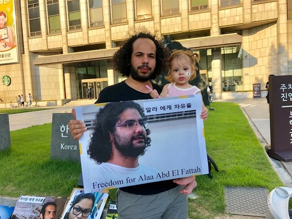 무삽 씨가 딸과 함께 이집트 정권에 비판적인 블로거 알라 압델 파타의 석방을 요구하는 사진을 들고 있다