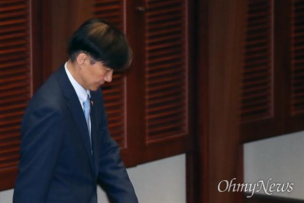 조국 법무부 장관이 26일 오후 서울 여의도 국회에서 열린 정치 분야 대정부질문에서 검찰의 압수수색 당시 수사 팀장과의 전화통화 사실이 알려지자, 고개를 떨군 채 자리로 향하고 있다.