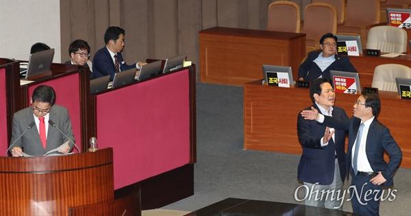 자유한국당 곽상도 의원이 26일 오후 국회 본회의장에서 열린 정치 분야 대정부질문에서 조국 법무부 장관을 '피의자 조국'이라고 부르자 더불어민주당 이원욱 원내수석부대표가 항의하고 있다. 이를 자유한국당 정양석 원내수석부대표가 말리고 있다.