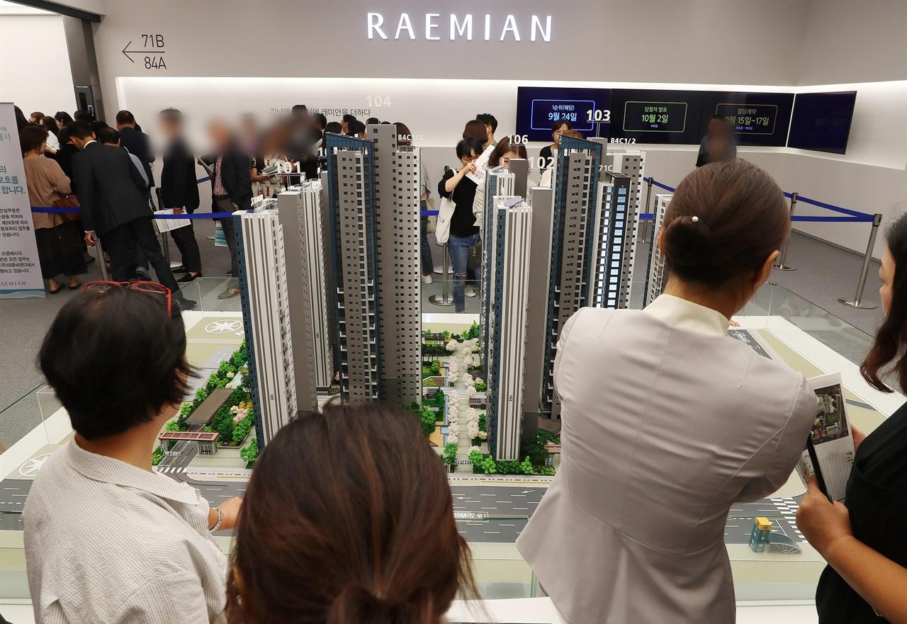 지난 20일 서울 송파구 래미안갤러리를 찾은 시민들이 '래미안 라클래시' 단지 모형을 살펴보고 있다. 이 아파트의 평당 분양가는 5000만 원에 육박했지만, 평균 청약 경쟁률은 100대 1을 넘겼다.