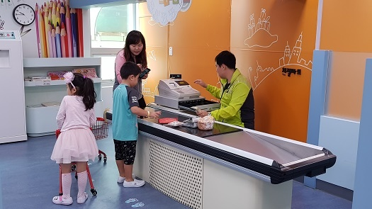 아이는 체험마트에서 시장을 보고, 아빠는 일일 점원으로 계산을 돕고 있다.